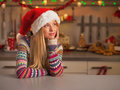 Thoughtful teenage girl looking on copy space in kitchen christmas decorated Stock Images
