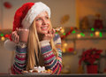 Thoughtful teenage girl in santa hat with cup of hot chocolate and christmas cookie decorated kitchen Royalty Free Stock Photography