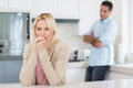 Thoughtful woman with blurred man in background in kitchen young women men standing the at home Royalty Free Stock Image