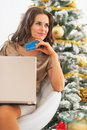 Thoughtful woman with credit card and laptop near christmas tree young Royalty Free Stock Images