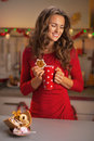 Thoughtful woman with cup of hot chocolate and christmas cookie young in red dress Stock Photo