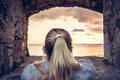 Thoughtful woman devoted into contemplation of beautiful sunset over sea through window of old castle with dramatic sky and perspe