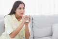 Thoughtful woman holding a cup of coffee sat on couch Royalty Free Stock Images
