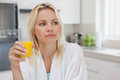 Thoughtful woman with orange juice in kitchen close up of a young the at home Stock Photography