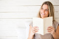 Thoughtful woman reading a book and looking happy Stock Photos