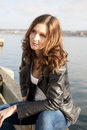 Thoughtful woman by sea in casual clothes with leather jacket sat halifax harbor in background Royalty Free Stock Image