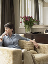 Thoughtful woman sitting on armchair with hand chin at home Royalty Free Stock Photography