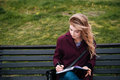 Thoughtful woman sitting on bench and writing in notebook outdoors Royalty Free Stock Photo