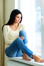 Thoughtful woman sitting on a window sill and looking outside young Stock Photos