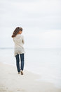 Thoughtful woman in sweater walking on beach young lonely rear view Stock Photo