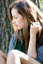 Thoughtful woman young seating near the tree Royalty Free Stock Photography