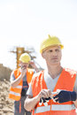 Thoughtful worker standing at construction site with colleague in background Royalty Free Stock Image