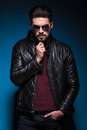 Thoughtful young bearded man wearing sunglasses and leather jacket looking at the camera Stock Photography