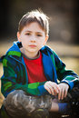 Thoughtful young boy in casual clothes sat in garden or countryside Stock Photos
