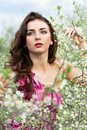 Thoughtful young curly brunette posing in flowering trees Stock Photos