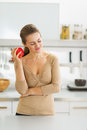 Thoughtful young housewife with apple in modern kitchen long hair red Stock Photography