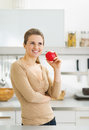 Thoughtful young housewife with apple in modern kitchen portrait of Royalty Free Stock Photography