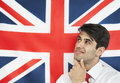 Thoughtful young man with hand on chin against british flag Stock Photos