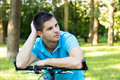 Thoughtful young man leaning on a bicycle in the park Stock Photos