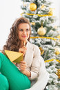 Thoughtful young woman with envelope near christmas tree in living room Royalty Free Stock Photography