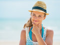 Thoughtful young woman in hat on beach pretty Stock Image