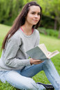 Thoughtful young woman holding a book Stock Images