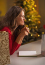 Thoughtful young woman making christmas list of presents in decorated kitchen Stock Image