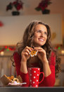 Thoughtful young woman in red dress having snack in kitchen christmas decorated Royalty Free Stock Photos