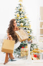 Thoughtful young woman with shopping bags near christmas tree full length portrait of happy Royalty Free Stock Photo