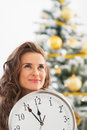 Thoughtful young woman showing clock in front of christmas tree portrait living room Stock Images