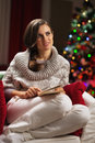 Thoughtful young woman sitting in armchair near christmas tree with book Royalty Free Stock Photography