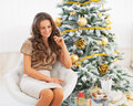 Thoughtful young woman sitting near christmas tree in living room Stock Photo