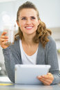 Thoughtful young woman with smoothie using tablet pc in kitchen Royalty Free Stock Photography
