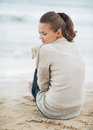 Thoughtful young woman in sweater sitting on lonely beach with long hair Royalty Free Stock Photography