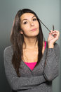 Thoughtful young woman twirling her hair attractive long brunette around fingers as she stares at the camera with a watchful Stock Photo