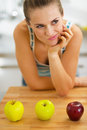 Thoughtful young woman and two green and one red apple on cutting board Stock Image