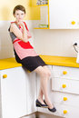 Thoughtful young woman wearing apron sat on units in modern kitchen Royalty Free Stock Photo