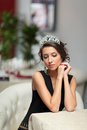 Thoughtfull girl beautiful in evening dress with a tiara on her head sits in a chair Royalty Free Stock Photography