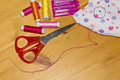 Thread needles scissors and a toy on the table sewing kit wooden Royalty Free Stock Images
