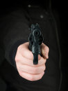 Threat at gunpoint closeup of the hand of a person dressed in black pointing a gun towards the viewer Stock Photo