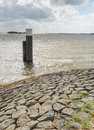 Threatening clouds above the water wooden bollard and a rough surface caused by stormy weather Stock Photography