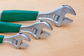 Three adjustable wrenches in row on wood Royalty Free Stock Photo