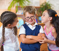 Three adorable schoolchildren having fun in classroom Royalty Free Stock Photography