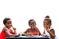 Three African girls doing thumbs up at table. Royalty Free Stock Photo