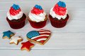 Three American patriotic themed cupcakes for the 4th of July with heart shaped american flag. Shallow depth of field. Royalty Free Stock Photo