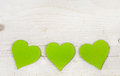 Three apple green hearts on white shabby style wooden background