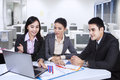 Three asian business team with laptop at office working Royalty Free Stock Photos