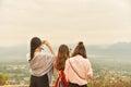 Three of asian ladies enjoy mountain view,use smart phone captur