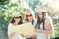 Three attractive girls looking for directions on a map at summer holidays vacation concept Royalty Free Stock Image