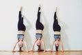 Three attractive young women doing handstand yoga asana in sports studio, Adho Mukha Vrksasana.